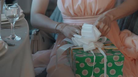obter : Young pretty woman packs gift in middle size green pattern box with white tapes and big attractive bow. Female wears in formal silky orange long dress. She ready to wish all best and celebrate with other guests.