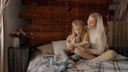 juntar : Attractive mother is holding her little girl with tenderness and reading fairy tales before sleeping. Young daughter is careful listening stories in bedtime to get good mood and happy emotions for relaxing. Stock Footage