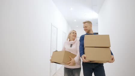 belongings : Charming lovely real couple is carrying to move in new big bright home. Man and young pleasant woman bring cartoon boxes with all stuff to empty house. They are smiling and sharing joy and happiness together. Stock Footage