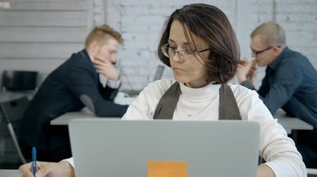 solicitor : Beautiful lawyer agent is working with computer at the office. Pretty intelligent women in round glasses and create main business strategy for company to make new finance project successful and stable.