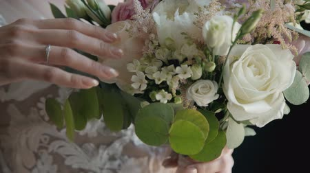 csatlakozott : Bride holding bouquette on wedding ceremony. Whire roses, leafs and flowers are there in beautiful floral composition. Stock mozgókép