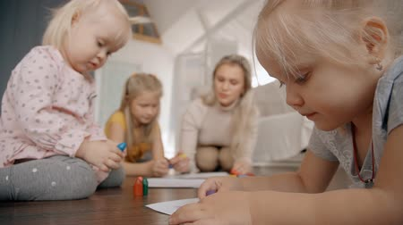 értékelés : Three girls and babysitter drawing on floor of cozy apartment. Blond sisters developing creative mond and assistant taking care of them sitting near.