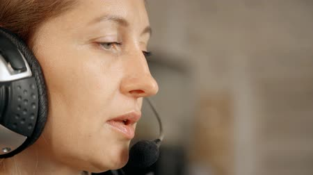 přátelský : Face of woman working as hotline consultant. Callcenter management using headphnes talking to customer and giving professional advice.
