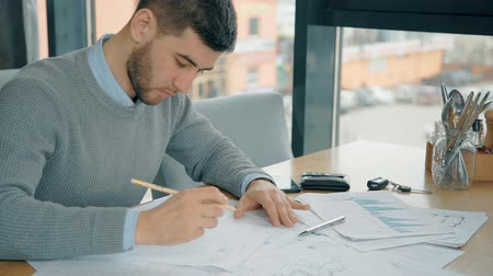 неформальный : Handsome entrepreneur is working with new project sitting at desk in cafe, young bearded director is doing work, writing on financial documents at table in bright room. Concept: startup, corporate, workplace.