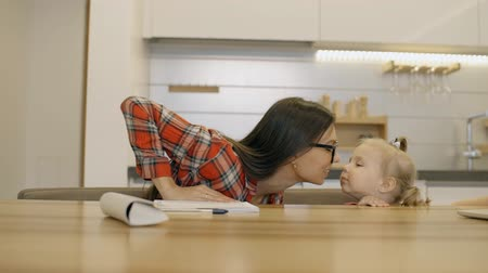 beijos : Young caucasian woman kissing little girl sitting at table in home kitchen, happy mother and adorable daughter are having good time at desk in modern bright interior. Concept: childhood, enjoying day, relationship.