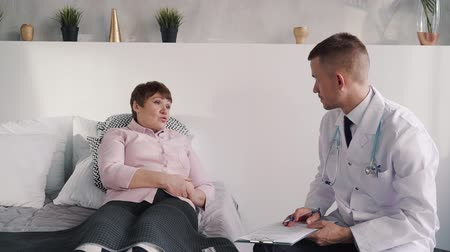 диагностировать : Retirement patient is talking, listening and consulting with helping doctor about diagnosis at the home office. Medical technology analysis for mature woman. Professional report conversation and discussion is caring about senior woman. Стоковые видеозаписи