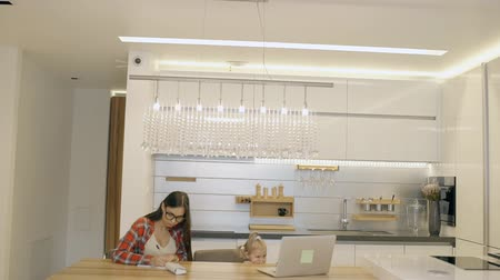 meia idade : Young mother and little daughter spending time together in modern kitchen at home. Female blond toddler watching animated films on the laptop on wooden table and woman with long hair in glasses sitting and writing in notebook.