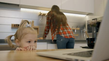 раковина : Blond female toddler watching animated videos on the kitchen while her mother washing sink. Little girl sitting at the wooden table with bran-new laprop on and young woman with long hair cleaning modern furniture. Indoors.