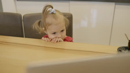 pokrývka hlavy : Little girl sitting at the kitchen table. Blond female infant with brown eyes put her hands to the wooden desk and holding her head on them, being bored, and waiting for mother. Portrait. Indoors. Dostupné videozáznamy