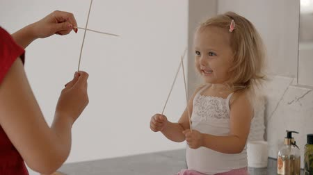приехать : Little blond girl and female babysitter playing with wooden skewers in bathroom. Beautiful happy child laughing enjying the game waiting for parents come. Стоковые видеозаписи