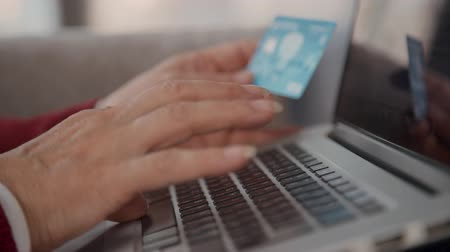 дебет : Close up retired female hands typing credit card number on laptop computer keyboard. Senior shopper using online electronic payment technology for internet shopping. Стоковые видеозаписи