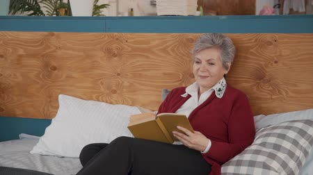 daily : Retired female pensioner relxing in bedroom reading fiction book. Aged woman lying on stylish bed with happy face and enjoying free time. Portrait.