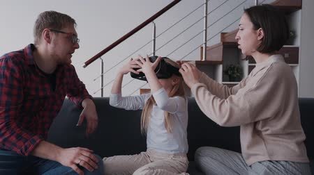 interativo : Attractive little girl is trying new vr glasses new mother and father. Family is sitting on sofa and wife husband couple is helping daughter with successful using of smart digital device of vitual reality. Stock Footage