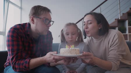 gratulací : Young cheerful daughter is blowing candles on white birthday cake with family at home. Mother and father is helping to girl and they all laughing together. Indoors celebration party and cute congratulations.