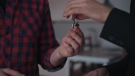 estate agency : Man is getting key from new own flat in close view. Family happy day of successful relocation to buying apartment. Home for people with secure access. First real estate agreement and bargain with realty agency. Stock Footage