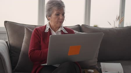 durulması : Serious, confident and focused elder lady in casual clothes sitting on couch in apartment room. She holding her modern laptop on knee and looking at cellular display with calm face