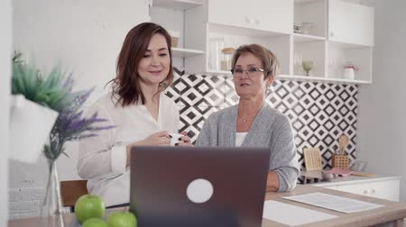 rejoice : Elderly mother and adult attractive daughter drinking beverage and talking near laptop pc. Two woman spending time together in bright room with modern interior and natural soft light