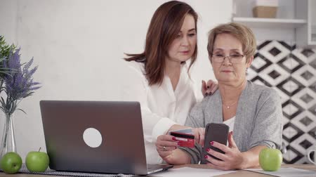 película de filme : Good-looking mature and mid-aged woman spending free time together using cellular and plastic card for shopping. They sitting in bright and stylish modern interior with soft daylight and smiling