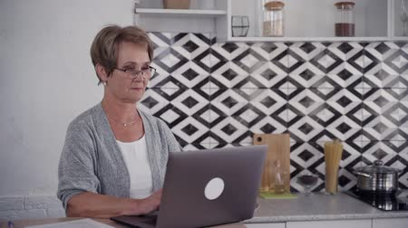 silvery : Senior woman is sitting at the table and working using digital computer technology. Aged grandparent with eyeglasses in slow motion. Successful grandmother looking professional and modern with wireless laptop.