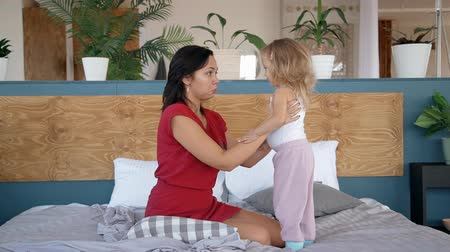 anne : Woman is sitting in bed and playing with little cute daughter. Couple is smiling and laughing in bedroom together. Caucasian young mother and child have fun play with morning kiss. Parent love and happy rest.