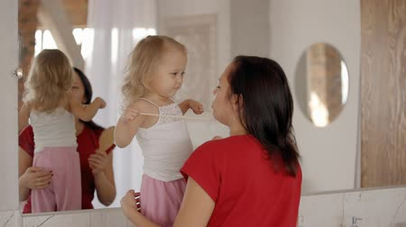 abraço : Cute happy little girl is standing near mirror with cheerful young mother. Bathroom background interior and adorable playing of two funny woman. Casual positive leisure of mom and child. Relaxing happiness.