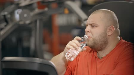 weight training : Chubby overweight man is holding bottle of water and drinking for little break between heavy exhausted workout training. Sweaty lazy male with fat body is tired and struggle for health sport concept. Stock Footage