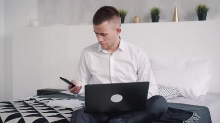 odaklanma : Confident and focused busy man in formal wear clothes sitting on bed in bright apartment with light interior. He looking at his modern smartphone display and holding laptop on knees
