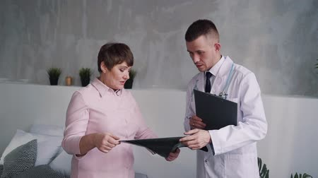 phd : Qualified and smart doc talking with matured and brunette hair woman in bright apartment about x-ray picture. They standing inside flat room and sigh insurance document with patient