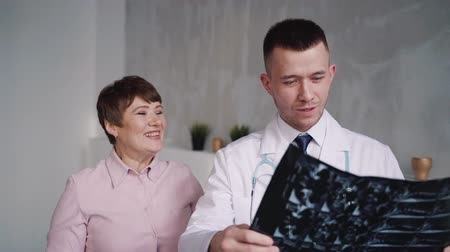 prescribe : Educated and handsome practitioner visiting beautiful middle-aged and illness woman in her house with nature soft light. They speaking about her x-ray picture and prescribe treatment Stock Footage
