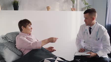 ajánlás : Young and professional doctor speaking with matured woman in bright apartment with light interior room about her illness. He listens her complaints on temperature and prescriptions treatments