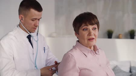 amadurecida : Attractive, young and professional doctor using stethoscope and listening his matured and brunette hair patient. They standing inside apartment with natural and soft daylight with calm face Stock Footage