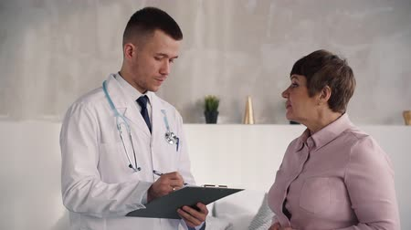 phd : Smart and confident physician speaking with matured woman inside light flat with modern interior. They looking to each other with nice smile on face discuss treatment and progress in women health Stock Footage