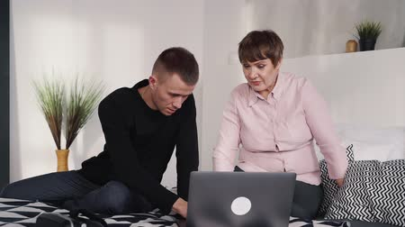 amadurecida : Serious and attractive man in casual wear sitting inside bedroom in apartment or modern flat with his mother in pink shirt. They using modern laptop and looking on his monitor or display