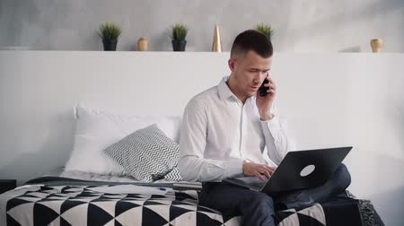 нетбук : Concentrated and serious, handsome man in white shirt and black pants sitting in bright room inside nice light flat. He speaking on modern smart telephone and using his laptop at home Стоковые видеозаписи