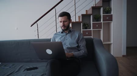 jel : Formalwear boss is sitting on sofa and working using computer and phone at home. Adult businessman is confident and smart entrepreneur with touchscreen technology of wireless networking device. Tapping gadget and 360 view of man.