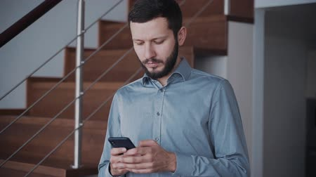 jel : Man is standing and chatting with people using smartphone for business and communication at home. Businessman is messaging with no expression on face holding modern technology network smart phone with touchscreen. Stock mozgókép