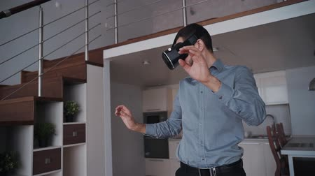 simülasyon : Man is standing and using smart digital vr technology gadget by gesture interaction motion. Professional tech company and creative successful project of virtual reality glasses production. Office background. Stok Video