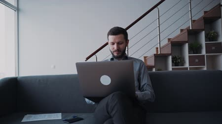 jel : Man is sitting on sofa and working using wireless laptop. Professional digital technology of corporate workplace and online removal connection. Information business and modern browsing for serious networking job.