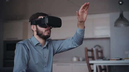 jel : Fun man is playing by modern virtual reality computer technology glasses. Digital future equipment for gaming and working at home apartment. Excited video game and casual relax concept with living room background.