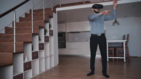 для взрослых : Serious man is standing and working using new virtual reality mask for modern lifestyle. Video screen with excited digital technology of vr glasses. background interior concept of living room with desk and working equipment.