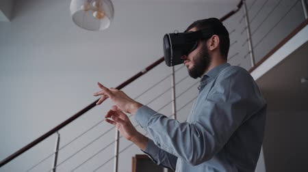 для взрослых : Man is standing in center of living room and typing information using digital technology of virtual reality glasses. Adult male is working with modern equipment for online chatting lifestyle at home.
