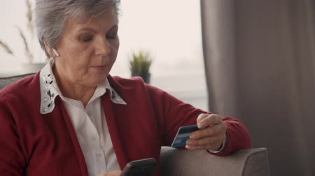remotely : Portrait of aged female consumer typing credit card number on smartphone screen. Senior woman using application for shopping, banking, purchasing online.