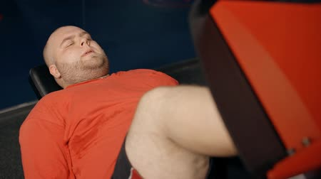 quadriceps : High angle top view of attractive and overweight young man in colorful orange t-shirt. He making exercise on leg press machine inside new city gym feeling tired and intense in muscles