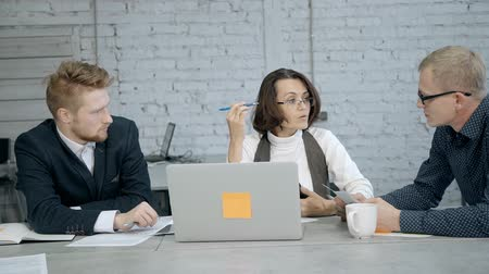 formální : Concept of communication in organization. Successful businessperson in formal wear clothes working inside modern workstation office with loft interior. Mature woman and man making conversation