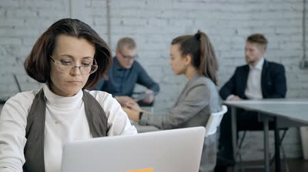 vzdálený : Clever, professional and confident person working indoor modern work space office with loft interior. Mature woman using laptop and sitting behind table against her colleagues on blurred background