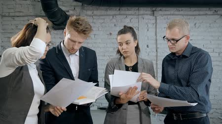 collaborating : Concept of communication in organization. Qualified people in formal wear clothes working indoor modern work space office with loft interior. Woman and man standing with document in hands and talking Stock Footage