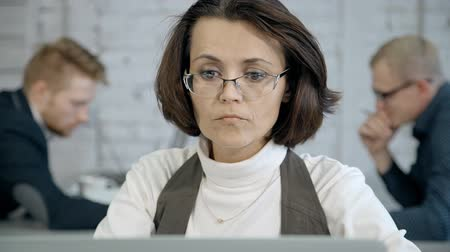 correio : Intelligent, professional and qualified specialists female working inside modern office with loft interior work place. Woman looking on laptop display and reading or sending mail for colleagues Stock Footage