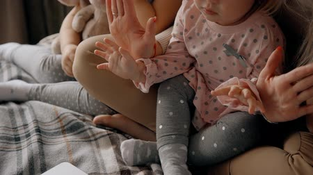 girl claps : Cheerful and attractive mother with her little kids playing and clapping in hands. They spending time together sitting on comfort bed in cozy bedroom with modern interior and natural soft light Stock Footage