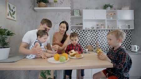 отпрыск : Big or large family concept. Two happy and smiling parents spending free weekend time with they kids at cozy and comfort home. Mather, father and three children sitting on kitchen and eating Стоковые видеозаписи