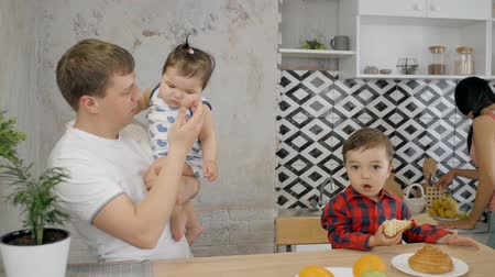 отпрыск : Happy and charming father spending free time with his little and charming kids. Smiling man standing in kitchen room near calm face son and holding little toddler daughter on hands Стоковые видеозаписи